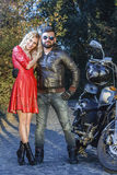 Ο άνδρας στη μοτοσικλέτα με μια προκλητική νέα γυναίκα στο κόκκινο φόρεμα ο δρόμος Στοκ φωτογραφία με δικαίωμα ελεύθερης χρήσης