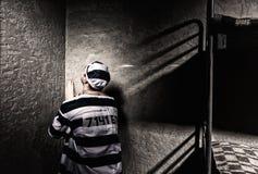 Ο άνδρας φυλακισμένος κάθεται στη γωνία και προσεύχεται σε μικρές δημόσιες σχέσεις Στοκ Εικόνα
