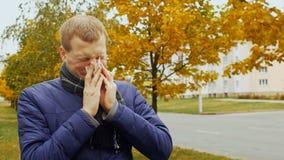 Ο άρρωστος ή άρρωστος άνδρας φυσά μια μύτη ` s στο υγιεινό χαρτομάνδηλο λόγω του ιού γρίπης γρίπης απόθεμα βίντεο