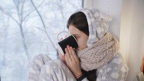Ο άρρωστος λυπημένος έφηβος κοριτσιών κάθεται από το παράθυρο το χειμώνα στις θερμές πυτζάμες, πίνοντας το καυτό τσάι από ένα φλυ φιλμ μικρού μήκους