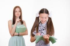 Ο δάσκαλος εξετάζει το σπουδαστή με ένα σημειωματάριο Στοκ Εικόνα