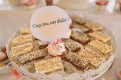 Ο άσπρος δίσκος μετάλλων με τα τετραγωνικά κέικ και ένα cupcake με το μήνυμα σε ρουμανικό ` Dragostea ε dulce `, αγάπη μετάφρασης στοκ εικόνες