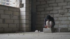 Ο άστεγος θερμαίνει κοντά στη μικρή φωτιά στο εγκαταλειμμένο κτήριο απόθεμα βίντεο