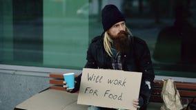 Ο άστεγος νεαρός άνδρας ικετεύει για το φλυτζάνι τινάγματος χρημάτων για να πληρώσουν οι άνθρωποι προσοχής που περπατούν κοντά στ στοκ φωτογραφία με δικαίωμα ελεύθερης χρήσης