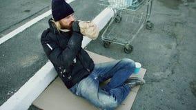 Ο άστεγος νεαρός άνδρας στα βρώμικα ενδύματα πίνει το κάρρο πλησίον αγορών συνεδρίασης οινοπνεύματος στην οδό στην κρύα χειμερινή Στοκ Φωτογραφία
