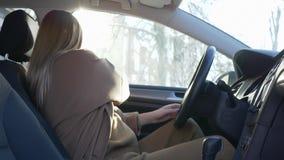Ο έγκυος οδηγός κοριτσιών που προετοιμάζεται για το ταξίδι ντύνει μια συνεδρίαση ζωνών ασφάλειας πίσω από τη ρόδα στο όχημα στο b φιλμ μικρού μήκους