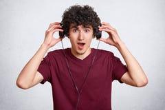 Ο έκπληκτος νεαρός φορά τα σύγχρονα ακουστικά, ακούει την απροσδόκητη δυνατή μουσική ή ο ήχος, κρατά το σαγόνι μειωμένο, φορά την στοκ εικόνες