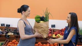 Ο έμπορος δίνει τα λαχανικά στη έγκυο γυναίκα φιλμ μικρού μήκους