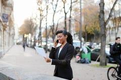 Ο έμπορος που αποκτάται αυξάνει, όμορφη κυρία που στέκεται στην οδό με τα έγγραφα ι Στοκ Εικόνα