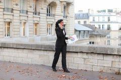Ο έμπορος που αποκτάται αυξάνει, όμορφη κυρία που στέκεται στην οδό με τα έγγραφα ι Στοκ Φωτογραφία