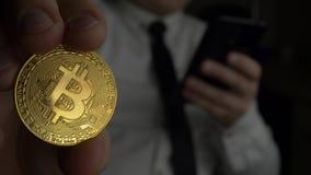 Ο έμπορος στο άσπρο πουκάμισο με το δεσμό που χρησιμοποιεί το μαύρο smartphone και κρατά το διαθέσιμο χρυσό νόμισμα bitcoin BTC φιλμ μικρού μήκους