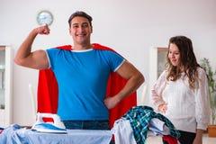 Ο έξοχος σύζυγος ατόμων ηρώων που σιδερώνει στο σπίτι να βοηθήσει τη σύζυγό του Στοκ Εικόνες