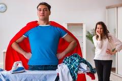 Ο έξοχος σύζυγος ατόμων ηρώων που σιδερώνει στο σπίτι να βοηθήσει τη σύζυγό του Στοκ εικόνες με δικαίωμα ελεύθερης χρήσης