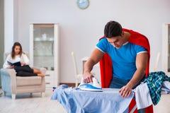 Ο έξοχος σύζυγος ατόμων ηρώων που σιδερώνει στο σπίτι να βοηθήσει τη σύζυγό του Στοκ φωτογραφίες με δικαίωμα ελεύθερης χρήσης