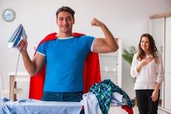 Ο έξοχος σύζυγος ατόμων ηρώων που σιδερώνει στο σπίτι να βοηθήσει τη σύζυγό του Στοκ φωτογραφία με δικαίωμα ελεύθερης χρήσης
