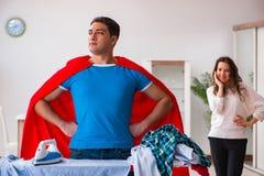 Ο έξοχος σύζυγος ατόμων ηρώων που σιδερώνει στο σπίτι να βοηθήσει τη σύζυγό του Στοκ εικόνα με δικαίωμα ελεύθερης χρήσης