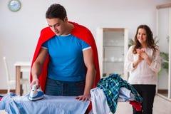 Ο έξοχος σύζυγος ατόμων ηρώων που σιδερώνει στο σπίτι να βοηθήσει τη σύζυγό του Στοκ Εικόνα