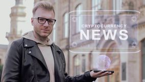 Ο έξυπνος νεαρός άνδρας με τα γυαλιά παρουσιάζει ειδήσεις ενός εννοιολογικές ολογραμμάτων Cryptocurrency φιλμ μικρού μήκους