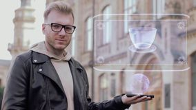 Ο έξυπνος νεαρός άνδρας με τα γυαλιά παρουσιάζει εννοιολογικό φλιτζάνι του καφέ ολογραμμάτων απόθεμα βίντεο