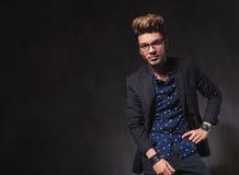 Ο έξυπνος νεαρός άνδρας που φορά τα γυαλιά θέτει στο σκοτεινό στούντιο Στοκ Εικόνες