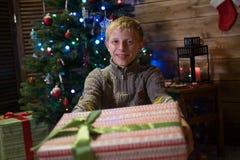 Ο έφηβος αγοριών δίνει ένα δώρο για τα Χριστούγεννα Στοκ Φωτογραφίες