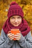 Ο έφηβος αγοριών με ένα φλυτζάνι του καφέ τσαγιού σε ένα ογκώδες μεγάλο άνετο μαντίλι και η ΚΑΠ burgundy χρωματίζουν Στοκ φωτογραφία με δικαίωμα ελεύθερης χρήσης