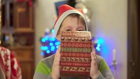 Ο έφηβος αγοριών σε ένα πουλόβερ άντεξε ένα δώρο και τα χαμόγελα στο υπόβαθρο των φω'των Χριστουγέννων απόθεμα βίντεο