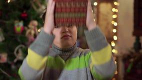 Ο έφηβος αγοριών σε ένα πουλόβερ άντεξε ένα δώρο και τα χαμόγελα στο υπόβαθρο των φω'των Χριστουγέννων φιλμ μικρού μήκους