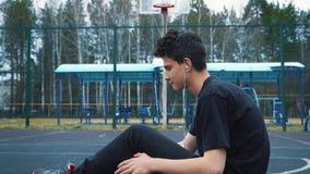 Ο έφηβος ακούει τη μουσική στο γήπεδο μπάσκετ απόθεμα βίντεο