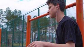 Ο έφηβος ακούει τη μουσική στο γήπεδο μπάσκετ φιλμ μικρού μήκους