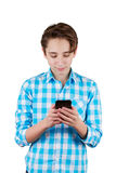 Ο έφηβος δακτυλογραφεί ένα μήνυμα στο τηλέφωνο Στοκ Φωτογραφία