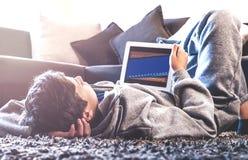 Ο έφηβος βάζει στο πάτωμα στο δωμάτιο Στοκ Φωτογραφία