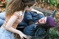 Ο έφηβος βοηθά το άστεγο άτομο Στοκ εικόνα με δικαίωμα ελεύθερης χρήσης