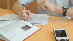 Ο έφηβος γράφει το κείμενο σε ένα copybook σε ένα μάθημα απόθεμα βίντεο