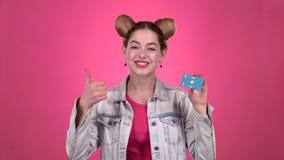Ο έφηβος διαφημίζει μια κάρτα και παρουσιάζει τους αντίχειρες Ρόδινη ανασκόπηση κίνηση αργή απόθεμα βίντεο