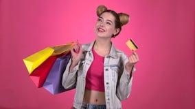 Ο έφηβος κρατά τις τσάντες αγορών και μια χρυσή πιστωτική κάρτα Ρόδινη ανασκόπηση κίνηση αργή φιλμ μικρού μήκους