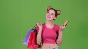 Ο έφηβος κρατά τις τσάντες αγορών και μια χρυσή πιστωτική κάρτα πράσινη οθόνη κίνηση αργή φιλμ μικρού μήκους