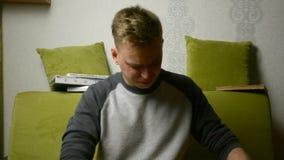 Ο έφηβος νεαρών άνδρων γελά στα προκατειλημμένα παλαιά μέσα εγγράφου ειδήσεων διαβάζοντας την εφημερίδα φιλμ μικρού μήκους