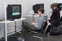 Ο έφηβος παίζει την κονσόλα τυχερού παιχνιδιού με την τηλεόραση σε Animefest Στοκ εικόνες με δικαίωμα ελεύθερης χρήσης