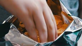 Ο έφηβος παίρνει με τα τσιπ πατατών χεριών στα πακέτα απόθεμα βίντεο