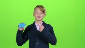 Ο έφηβος παρουσιάζει και γυρίζει κεφάλι του στην πιστωτική κάρτα σε μια πράσινη οθόνη κίνηση αργή φιλμ μικρού μήκους