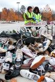 Ο έφηβος προσφέρεται εθελοντικά το είδος μέσω των πάνινων παπουτσιών στο γεγονός ανακύκλωσης Στοκ εικόνες με δικαίωμα ελεύθερης χρήσης