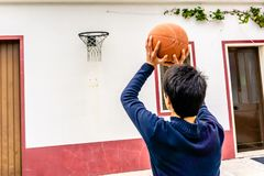 Ο έφηβος πυροβολεί την καλαθοσφαίριση προς τη στεφάνη που τοποθετείται επάνω από την πόρτα γκαράζ στοκ φωτογραφία