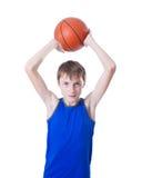 Ο έφηβος σε ένα μπλε πουκάμισο ρίχνει μια σφαίρα για την καλαθοσφαίριση απομονωμένος Στοκ Φωτογραφίες