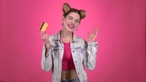 Ο έφηβος σε ένα ρόδινο θέμα με μια πιστωτική κάρτα είναι ευτυχής Ρόδινη ανασκόπηση κίνηση αργή απόθεμα βίντεο