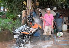 Ο έφηβος σε μια ρόδινη μπλούζα, μια ΚΑΠ και λαστιχένιες μπότες πλένει ένα μηχανικό δίκυκλο Μηχανικό δίκυκλο μηχανών στο λευκό στοκ εικόνες με δικαίωμα ελεύθερης χρήσης