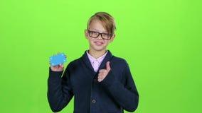 Ο έφηβος στα γυαλιά εξέτασε την πιστωτική κάρτα και παρουσίασε το δροσερό στην πράσινη οθόνη κίνηση αργή φιλμ μικρού μήκους