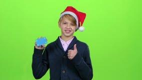 Ο έφηβος στο νέο καπέλο έτους με μια πιστωτική κάρτα παρουσιάζει όπως σε μια πράσινη οθόνη κίνηση αργή φιλμ μικρού μήκους