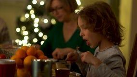 Ο έφηβος τρώει ήπια με ένα μαχαίρι και ένα δίκρανο Γεύμα οικογενειακών Χριστουγέννων Κανόνες της εθιμοτυπίας, συμπεριφορά στον πί απόθεμα βίντεο