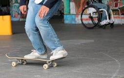 Ο έφηβος skateboarder στον πίνακα σαλαχιών με το άτομο στην αναπηρική καρέκλα Στοκ Φωτογραφία